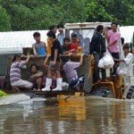 Flood affected people ride a tractor thr