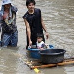 Man escorts son while wading through floodwaters in Nakhon Ratchasima province